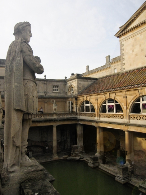 View of original bath from above, columns surround bath and statue in foreground.